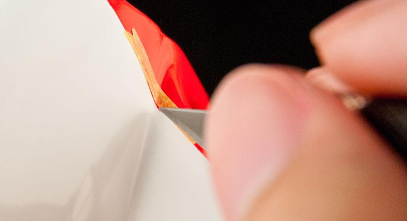 デザインナイフではみ出した塗料を削り取る