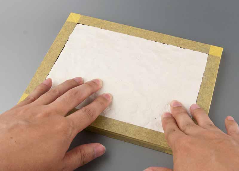 素手で粘土を敷き詰める