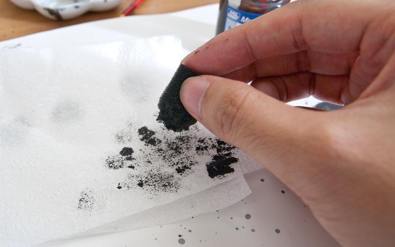 ティッシュでスポンジについた塗料を拭き取る作業